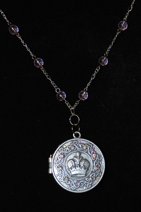 Silver tone royal crown on a beautiful locket with gem accents all on a silver tone 18 inch chain with pink bead accents