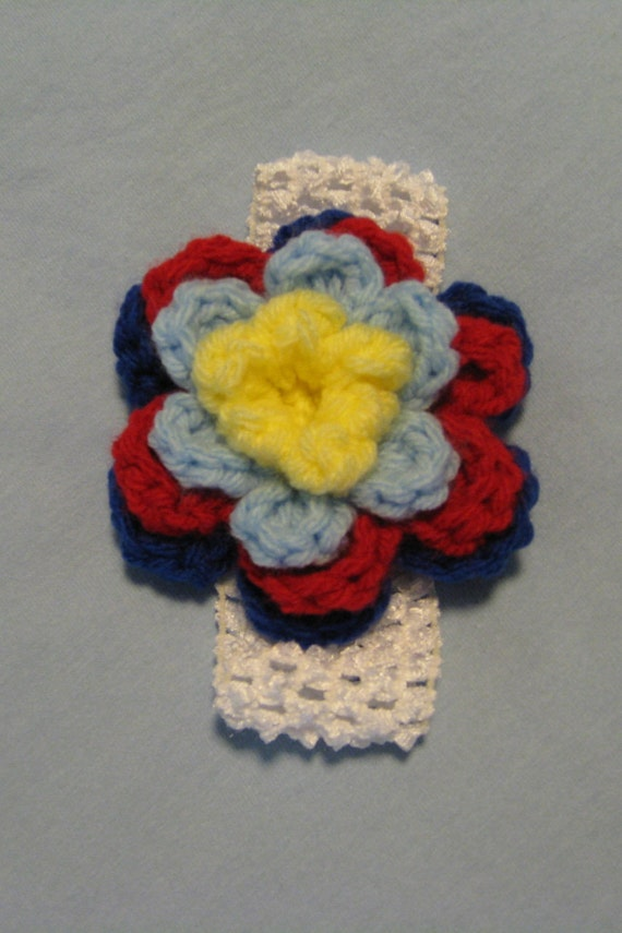 White baby head wrap with intricate crocheted flower in Autism Awareness colors