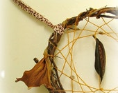 Gorgeous baby crib mobile - dream catcher weaved in mustard yarn and adorned with natural pods, seeds and a feather.