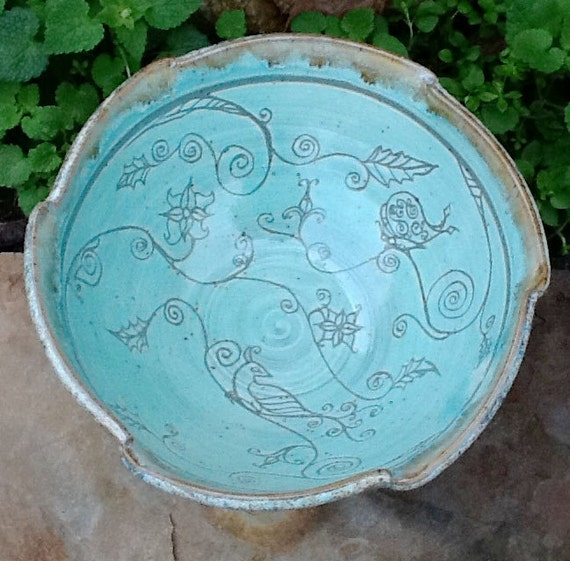 A Sgraffito Etched Serving Bowl displaying a bird and vines