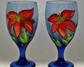 Tropical and festive hand painted Tiger Lily and buds in bold red and orange - Matching pair of Royal blue glasses