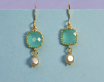 Angles and dangles. Square framed aqua faceted gem with a tiny cube glass pearl