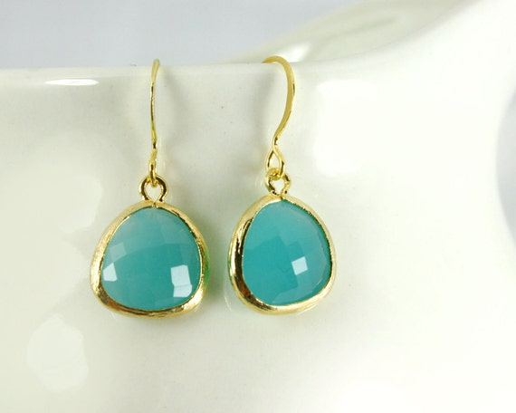 Aqua blue earrings opaque-ish with gold bezel setting. Framed and faceted