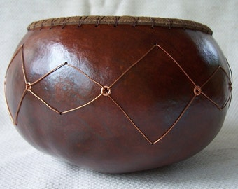 Medium cordovan gourd bowl with copper wire and eyelet diamonds pattern, leather and sea grass rim.  Item 1108.