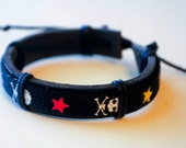 Skull with multicolored star black leather bracelet