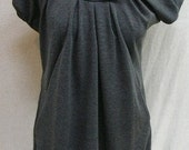 Gray tunic with high neck and draped.