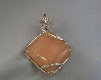 Pendant: Peach colored Quartz pendant wrapped in sterling silver