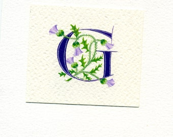 Initial letter 'G' handpainted in purple with Scots thistles on watercolor paper.