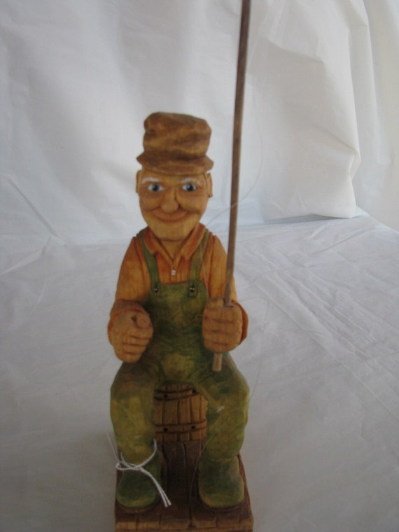 Handcarved fisherman with fishing pole