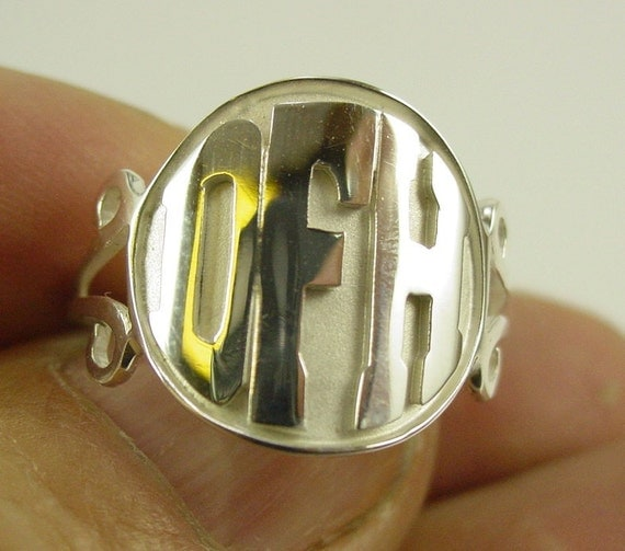 silver ring with  2-3  monogrammed initials,