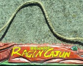 Ragin Cajun - Alligator - shaped sign in bright metallic red - this alligator definitely gives the sensation of red, hot sauce.