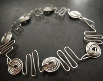 Silver wire wrapped bracelet with abstract, geometric design