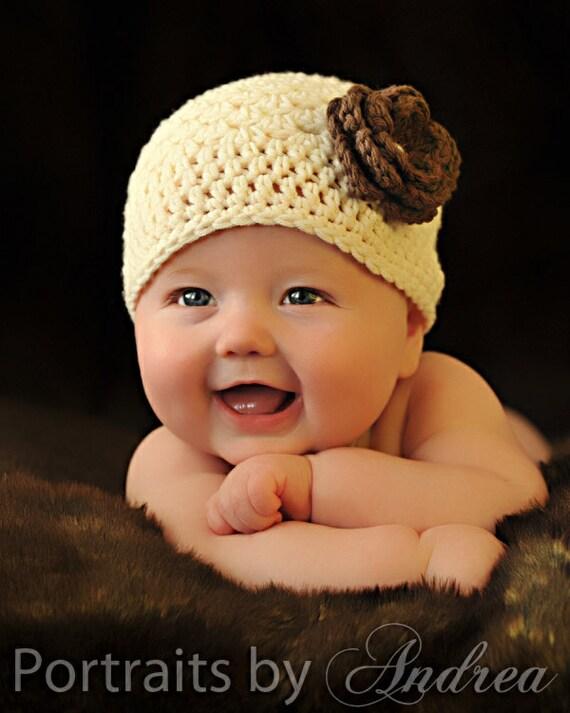 دختر نوزاد تازه متولد شده و یا 0 تا 3 ماه - کرم و قهوه ای یکنوع عرقچین کوچک کهمحصلین برسر میگذارند کلاه با گل - سرپا نگه داشتن عکس بزرگ