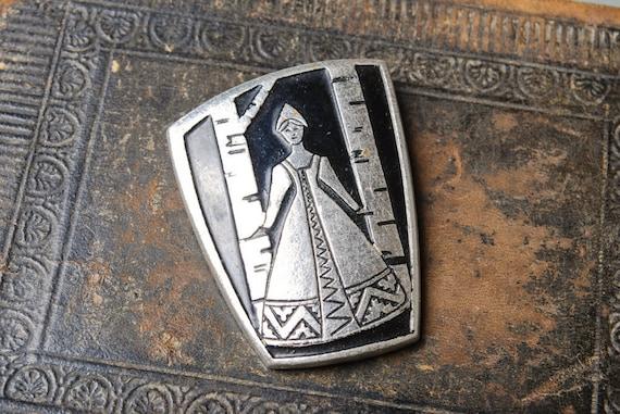 Vintage metal brooch. Woman in Russian national dress