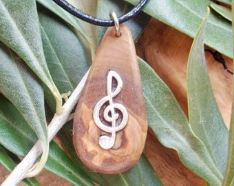 Musical pendant.  Hand carved Greek Olive wood necklace inlaid with Tibetan silver treble clef.