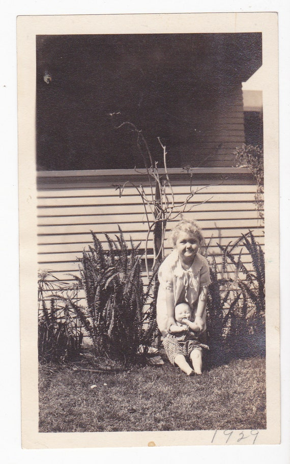 1920's Little girl holds baby doll in yard
