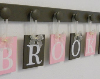 Baby Girl Personalized Wall Decorations Includes Wooden Name Plaque Letters and Pegs in Chocolate Brown and Light Pink.