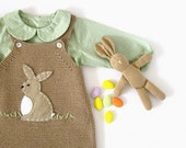 A knitted overalls in camel with a rabbit