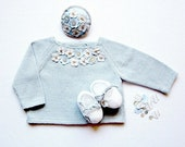 A knitted blue sweater for baby girl with little flowers
