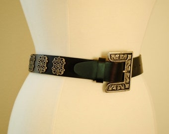 a vintage 80s black leather belt. a metal buckle with ornate details size small.