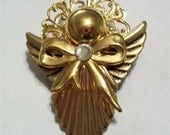 Angel pin with pleated skirt in gold tone