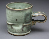 Coffee mug with splotchy dark green glaze