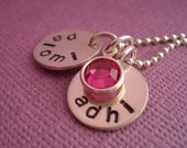 Customized hand-stamped names. Two sterling silver discs hanging with a crystal.