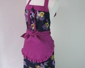 1950s vintage inspired apron with collar, vibrant floral pattern on a dark blue background, fully lined.