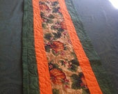 Fall Table Runner of pumpkins. Bright orange and green with muslin backing. Quilted with a leaf pattern