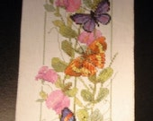 Narrow wall-hanging cross stitch with oodles of butterflies on the vine