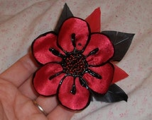 black and red poppy pin