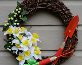 Grapevine wreath of yellow and white daffodils, orange shovel and rake, spring berries 19X19X6