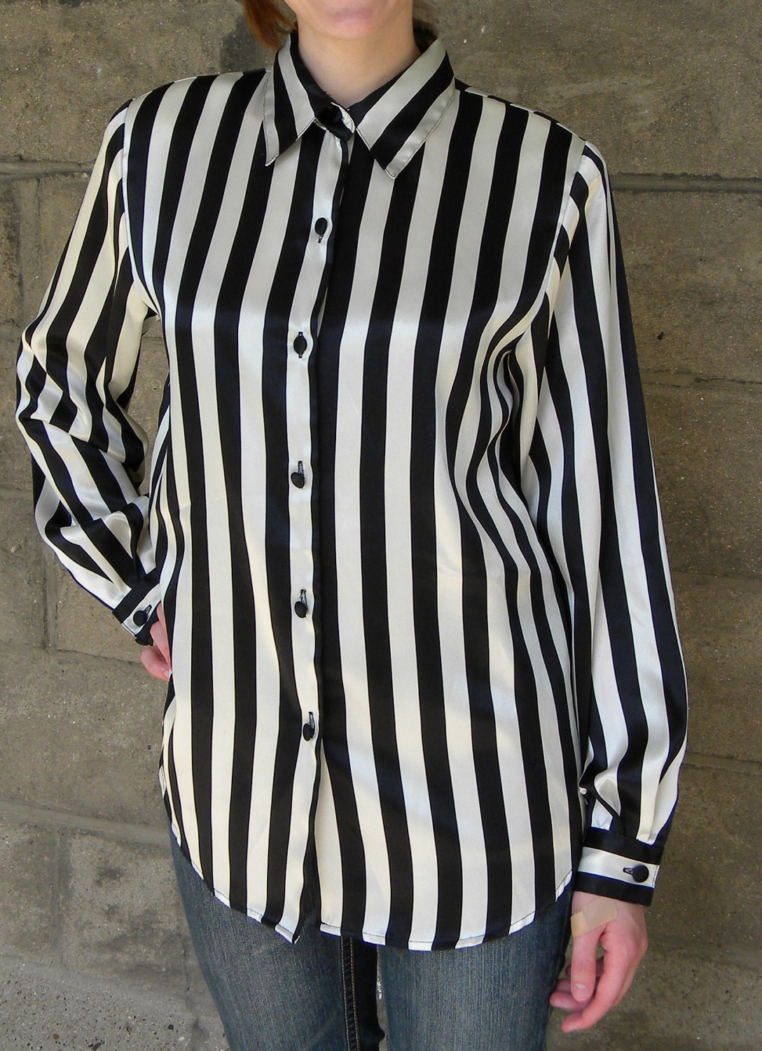 A black and white striped sleeveless blouse with pockets and buttons all the way down the front. Slight slits at the side and the back is slightly longer than the front.