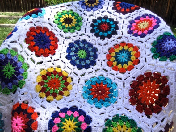 Kaleidoscope afghan with multicolors and white border.