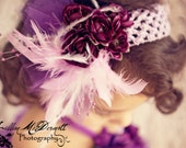 Purple crocheted headband with floral, pearl, and feather embellishments.