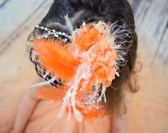 Exquisite orange headpiece with floral, feather, pearl and birdcage netting embellishments.