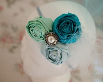 Vintage style shades of blue handrolled Rosettes with a button  and feather embellishment.