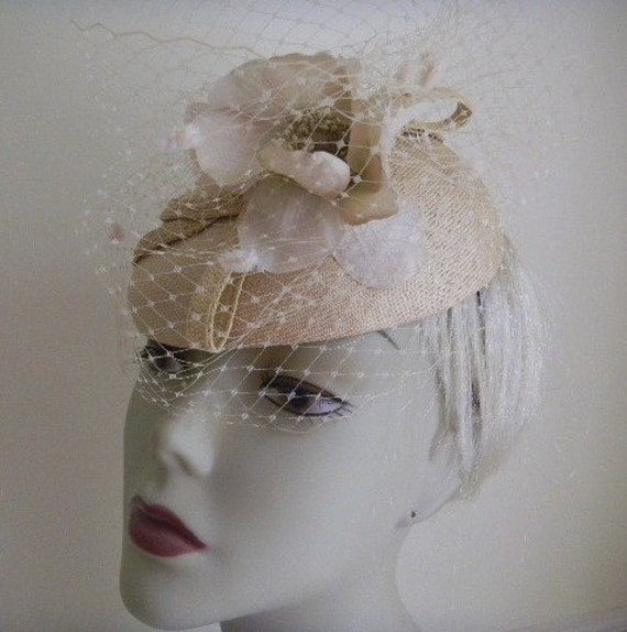 Fascinator  in shades of white and natural biege colours and with an off white veil