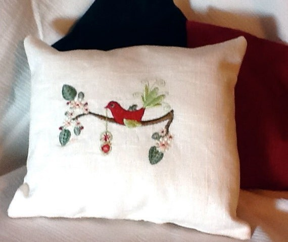 Bird decorating a tree for Christmas embroidered pillow
