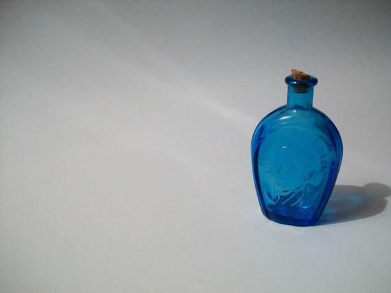 RESERVED tiny little horse shoe shaped blue bottle