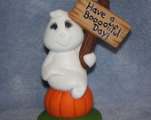 Handpainted ceramic Ghost sitting on a pumpkin with a sign to Have a Boootiful Day
