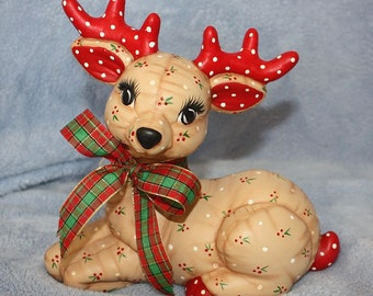 Ceramic Christmas Reindeer Laying hand painted with a Holly Berry print to look stuffed & a plaid ribbon