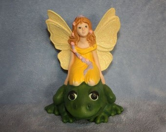 Handpainted Ceramic Fairy in yellow with sparkling wings riding a green frog