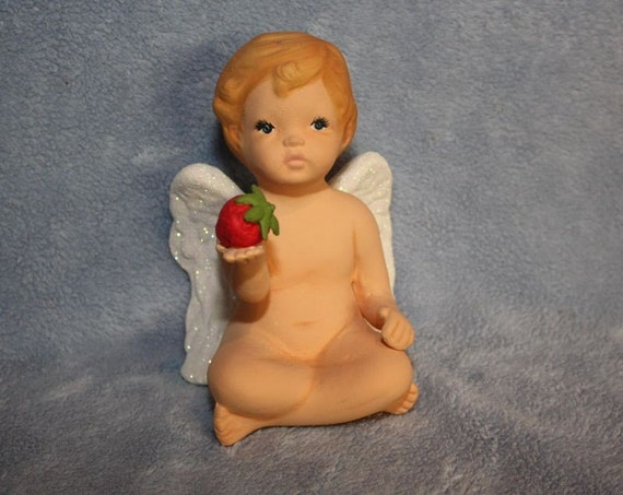 Handpainted Ceramic Cherub with sparkling wings and holding a strawberry