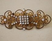 "Delicate filligree/wire with white stones ""squared"" in the heart of the brooch/pin"