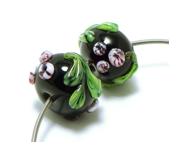 Lampwork beads pair pink flowers with green leaves on dark ink colored glass