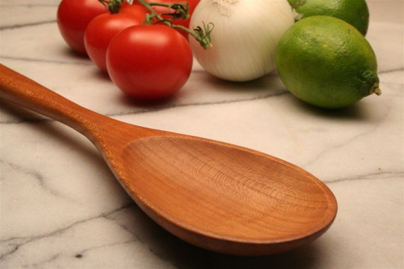 Wooden spoon for stirring with tasting spoon carved onto the handle made from cherry wood