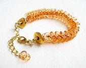 Braided bracelet in orange and gold, Chevron motif