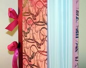 Pink book with bird pattern and ribbon spine