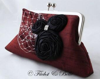 Burgundy silk clutch, black satin rosettes, leaf, and rhinestone